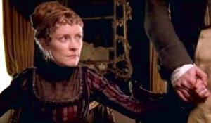 Fanny Dashwood, equally upset, holds onto her husband's hand.