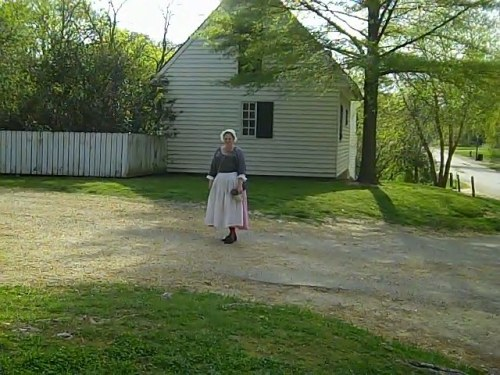 A comely maid walks home after a long day.