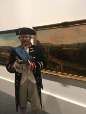 Image of a Georgian gentleman in Georgians exhibition reading first edition pride and prejudice with artwork