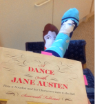 Image of Vic wears rival authors on her feet whilst reading Fullerton's A Dance With Jane Austen.