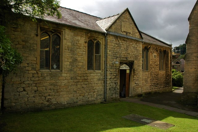 Photograph of the front of a modest stone building
